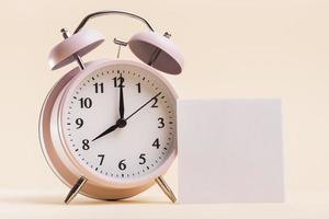 pink alarm clock with blank white adhesive note beige background. photo
