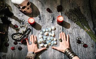 Manos de adivino con runas de piedra, interior místico. foto