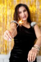 woman holding sparkler and balloon on golden background photo