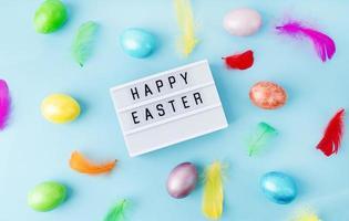 caja de luz feliz pascua decorada con huevos y plumas de colores brillantes foto