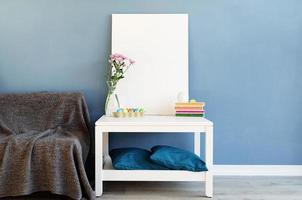 Simulacros de marco de póster blanco en la mesa de café en la habitación azul foto