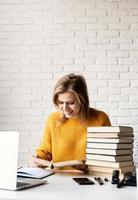 Young smiling woman in yellow sweater studying reading a book photo