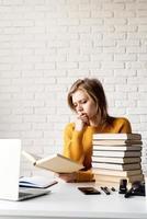 joven pensativa en suéter amarillo estudiando leyendo un libro foto