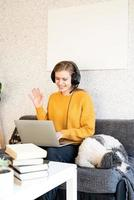 Young smiling woman in black headphones studying online using laptop photo