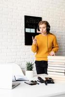 woman in headphones teaching online using video chat on laptop photo