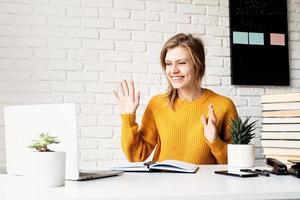 Mujer sonriente joven en suéter amarillo estudiando en línea usando la computadora portátil foto