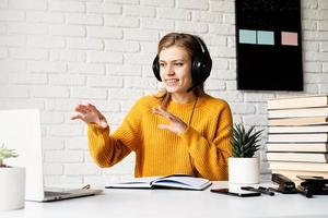 woman in headphones studying online using laptop talking in video chat photo