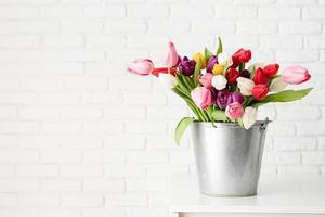 Bucket of tulip flowers over white brick wall background photo