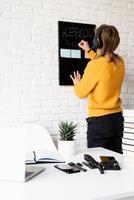 woman teaching online using laptop, writing on blackboard photo