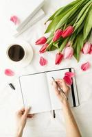 woman hands writing in notebook with tulips on white bed photo