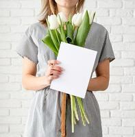 Mujer en vestido de rayas sosteniendo flores de tulipán blanco y tarjeta de felicitación foto