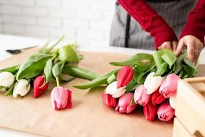 Woman florist making a bouquet of fresh colorful tulips photo