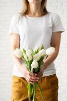 Young woman wearing blank white t-shirt holding tulips flowers photo