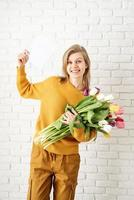 woman in yellow clothes holding bouquet of tulips and blank card photo