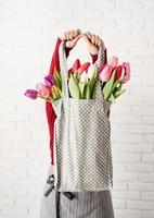 Mujer sosteniendo una bolsa de tela de lunares grises con coloridos tulipanes foto