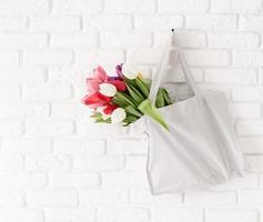 Gray fabric bag full of colorful tulips on white brick background photo