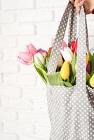 Mano de mujer sosteniendo una bolsa de tela de lunares grises con coloridos tulipanes foto