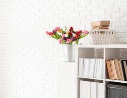 Bucket of tulip flowers next to the bookshelf over white brick photo