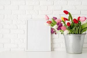 Bucket of fresh tulip flowers and blank frame photo