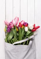 Gray fabric bag full of colorful tulips on white wooden background photo
