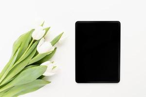 tulip flowers and mock up digital tablet top view flat lay photo