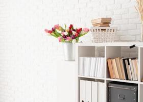 Bucket of tulip flowers next to the bookshelf photo