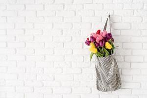 Bolsa de tela gris ful de coloridos tulipanes sobre fondo de ladrillo blanco. foto