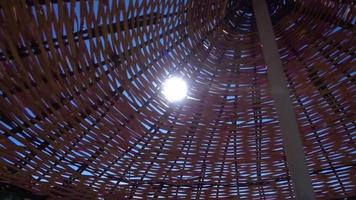 Sun Rays Shining Through Holes Of Wooden Umbrella On The Beach Surrounded video