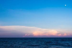 Clouds and moon in sunset sky over sea photo