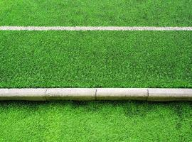 Texture of plastic artificial grass and concrete border of school yard photo