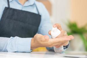 Empleado que usa la mano de limpieza de gel de alcohol para trabajar en la cafetería. foto