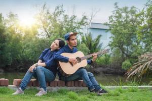 pareja asiática tocando la guitarra resto en verano foto