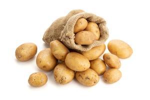 patatas nuevas en saco de arpillera aislado sobre fondo blanco. papa cruda foto
