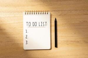 lista de tareas en el bloc de notas en espiral aislado en el escritorio de madera. endecha plana foto