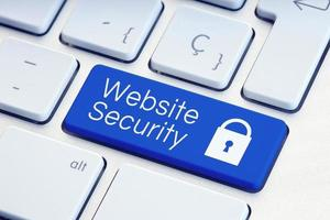 Website Security word and padlock icon on blue computer keyboard photo