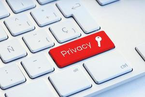 Privacy word and key icon on red computer keyboard photo