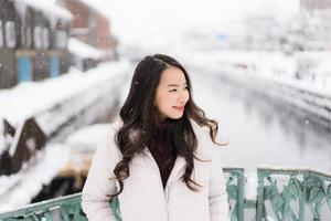 asian woman smiling happy for travel in snow winter season photo