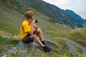 Young male photographer in the mountains photo