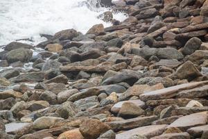 piedras y el mar en una playa de río de janeiro para el fondo. foto