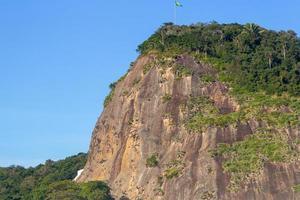 Helm Stone con la bandera de Brasil en la parte superior, visto desde la playa de Helm en Río de Janeiro, Brasil foto
