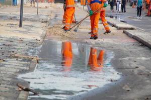 Los trabajadores de limpieza quitando la arena del paseo marítimo de la playa de Leblon en Río de Janeiro, Brasil foto