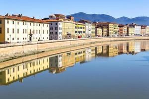 edificios en pisa reflejados en el río arno foto