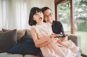 padre e hija asiáticos juegan videojuegos juntos foto