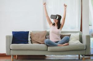 excited Asian woman in VR headset raising both hands up photo