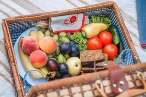 Cesta de picnic con fruta y pan de cerca foto