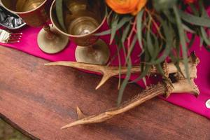 Decorated wooden table with flowers, candles, utensils photo