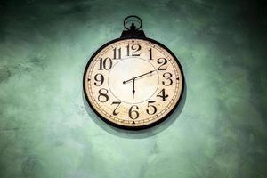Reloj vintage colgado en la pared verde foto