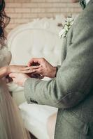 A closeup view of bride and groom exchanging rings, vertical image photo
