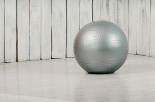 Grey fitball in a gym, light floor and background photo