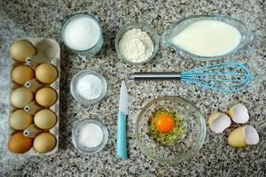 huevos, leche y otros productos en la mesa de la cocina. foto